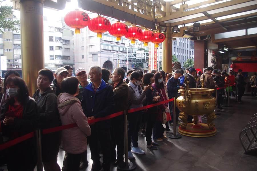 約有千名民眾一早志覺修宮排隊領取福袋,受到武漢肺炎疫情影響,不少人戴上口罩防疫。(許家寧攝)