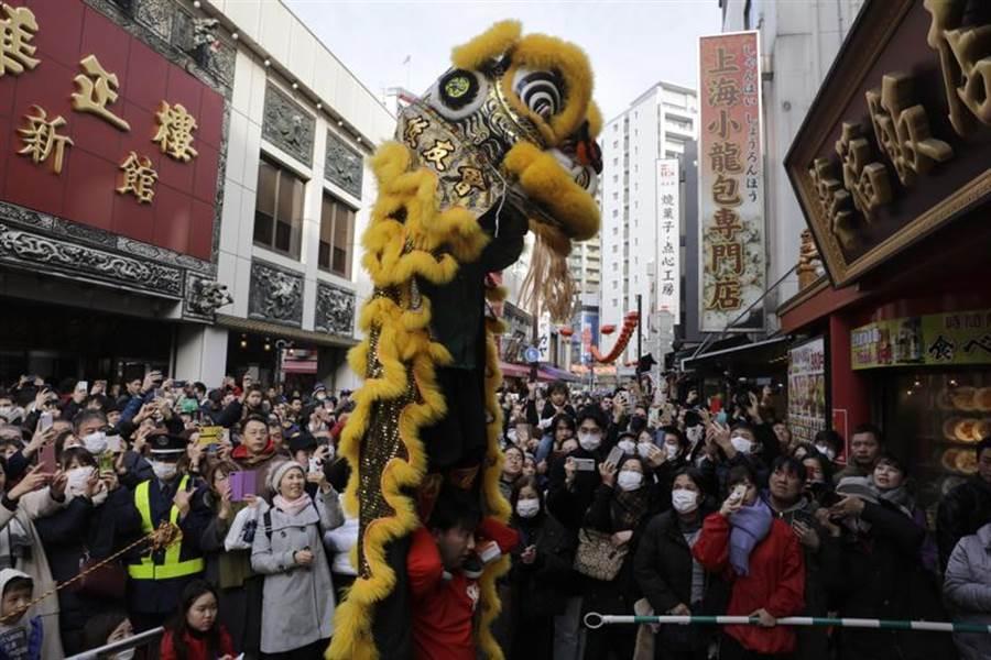 迎接春節到來,日本橫濱中華街25日舉行舞獅表演。為防武漢病毒,許多遊客都戴上了口罩。(美聯社)