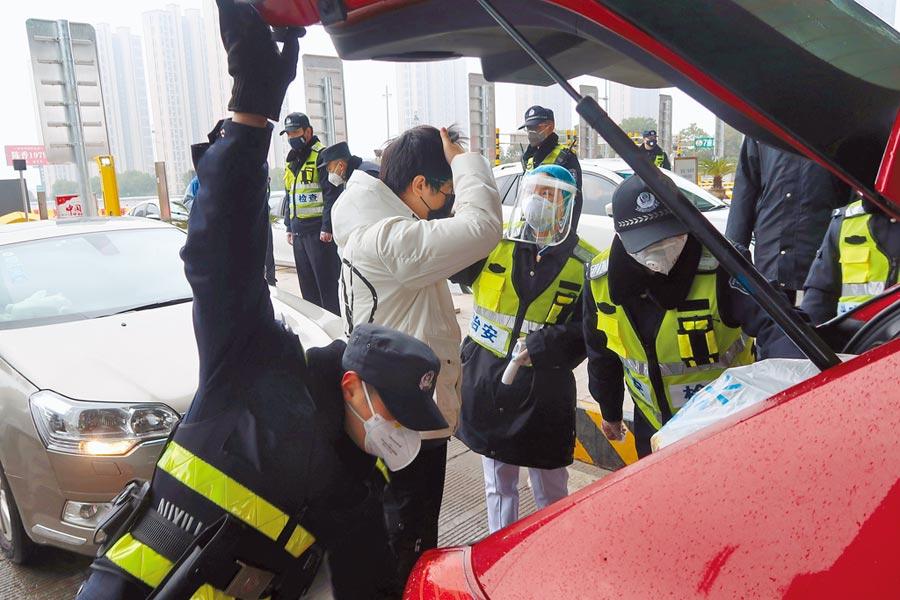 為了防堵肺炎疫情擴散,在湖北武漢附近的高速公路收費站,戴著口罩的警察加大檢查力度。(路透)