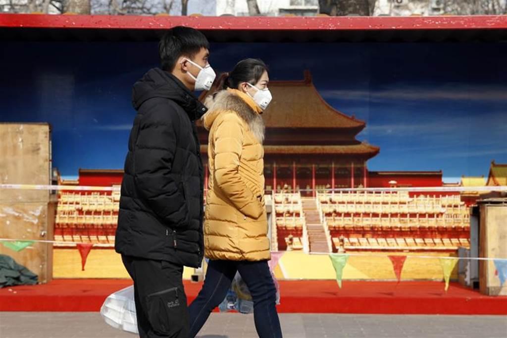 北京衛生健康委員會稱已有1男1女的武漢肺炎患者接受對症及中藥治療,已經治愈並於24、25日出院。圖為戴口罩外出的北京市民。(圖/中新社)