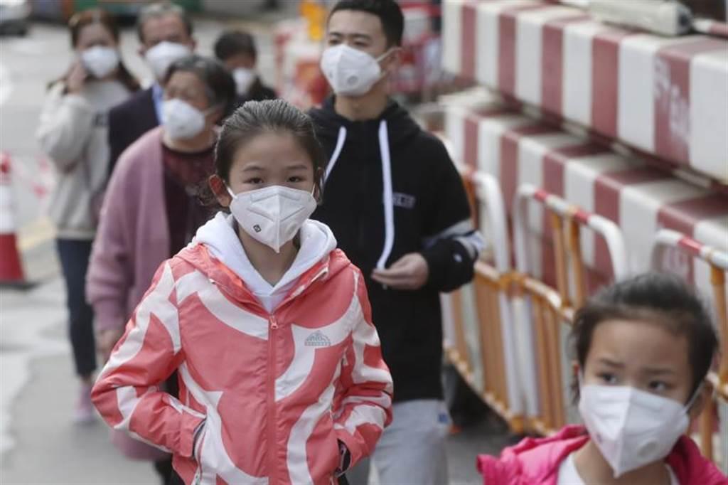 大陸遊客在香港戴著防護口罩。(美聯社)