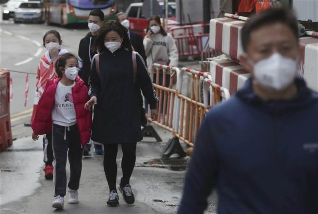 為了防止感染武漢肺炎,遊客26日紛紛戴上口罩,走在香港街頭。(美聯社)