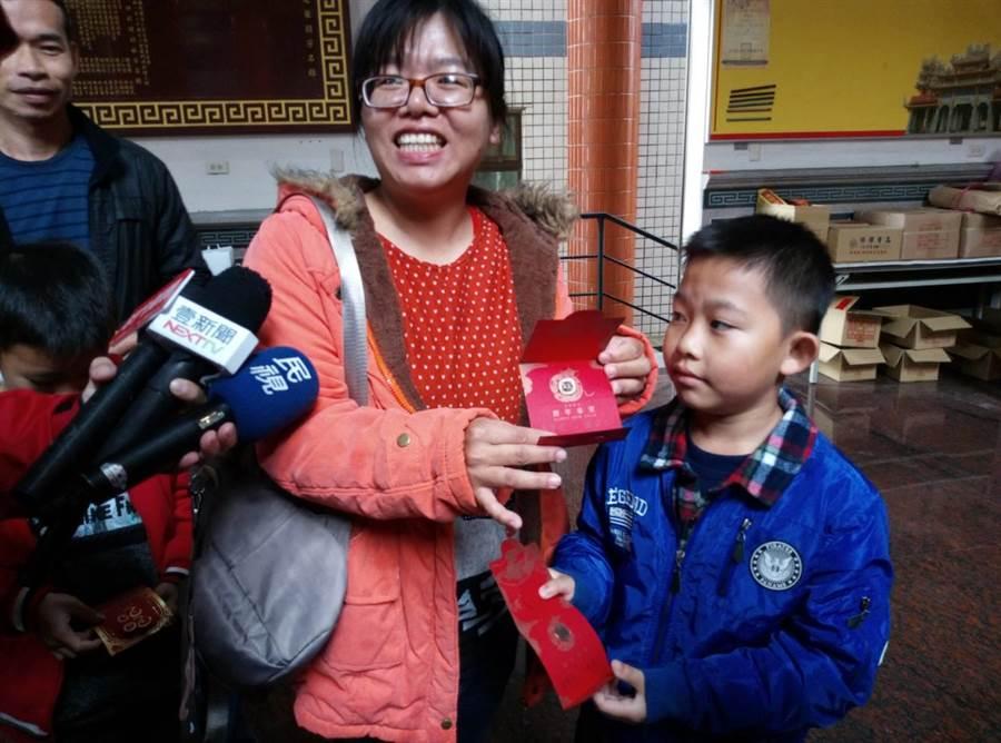 這位媽媽回娘家得知副總統當選人賴清德要發福袋,帶著兒子冒雨等了半小時終於領到,非常開心。(許素惠攝)