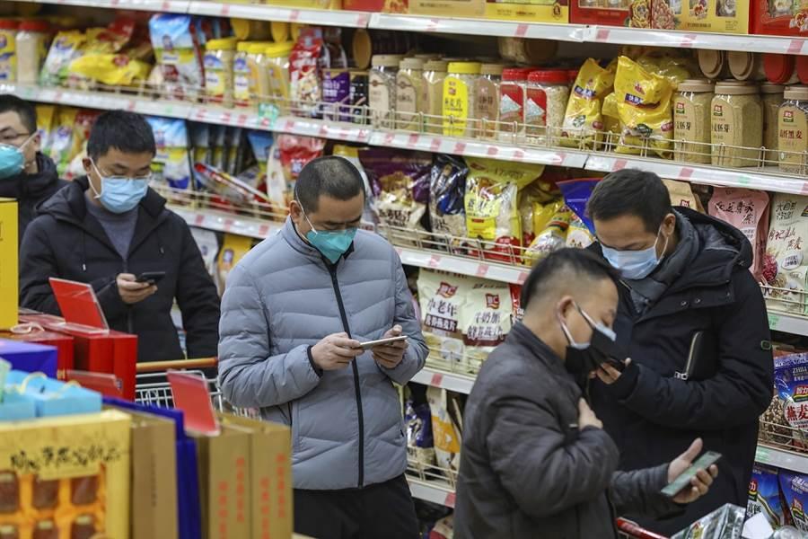 武漢疫情十分嚴峻,圖為當地民眾25日戴口罩在商場採購。(美聯社)