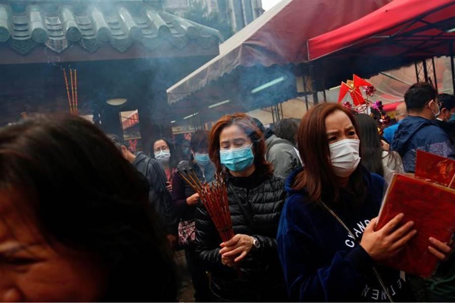過年香港居民到廟裡祈福,但由於新型冠狀病毒肆虐,人們紛紛戴著口罩上香。(路透社)