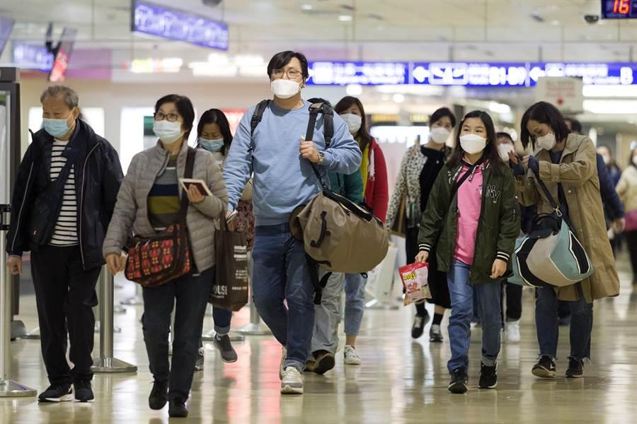 在台灣的武漢旅行團或湖北旅行團忙著離台的同時,受到大陸疫情擴散,有可能會增加封城的影響,前往大陸旅遊的台灣旅行團也急著自願提早結束旅遊行程,趕著回到台灣家。圖為26日下午入境旅客,幾乎人人都戴上了口罩。(陳麒全攝)