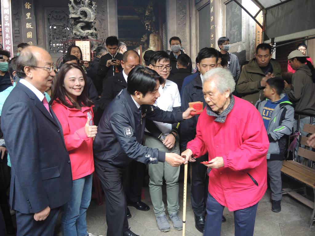 準副總統賴清德(中)年初三到新竹城隍廟參香祈福,發送福袋給拜拜民眾。(邱立雅攝)