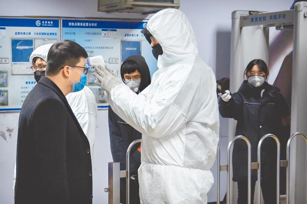 旺旺集團為防疫新型冠狀病毒肺炎,無償提供水神消毒除菌產品,25日首批物資運抵武漢。圖為地鐵站為乘客測量體溫。   (美聯社)