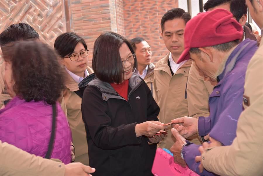 蔡英文總統(左三)28日中午前往義民廟,親手發放福袋,還一一領取民眾道聲「新年快樂」。(莊旻靜攝)