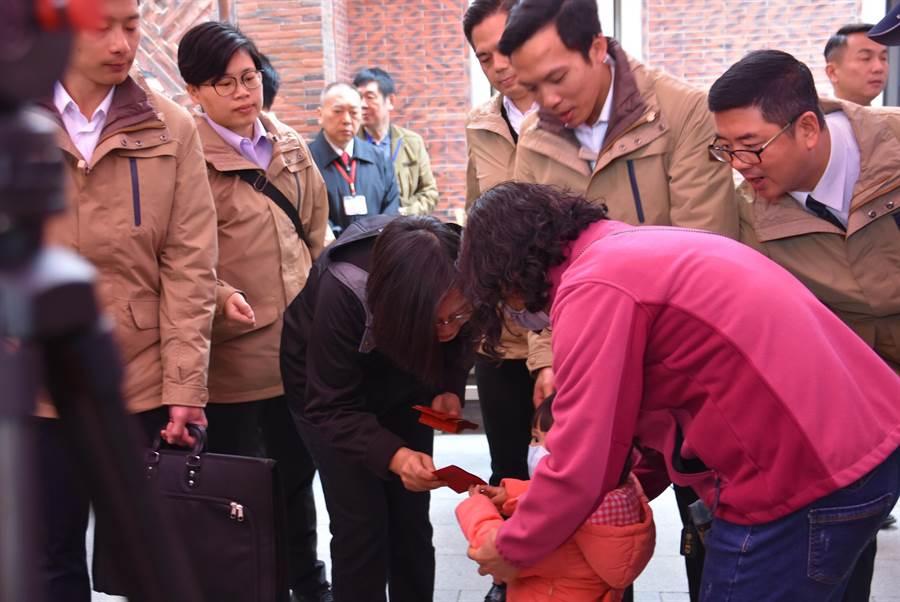 蔡英文總統(左二)28日中午前往義民廟發放福袋,還有幼童、小孩排隊領取。(莊旻靜攝)