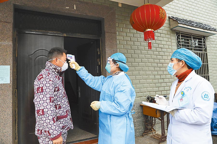 防疫人員在大陸東部浙江省杭州市檢查體溫。(美聯社)