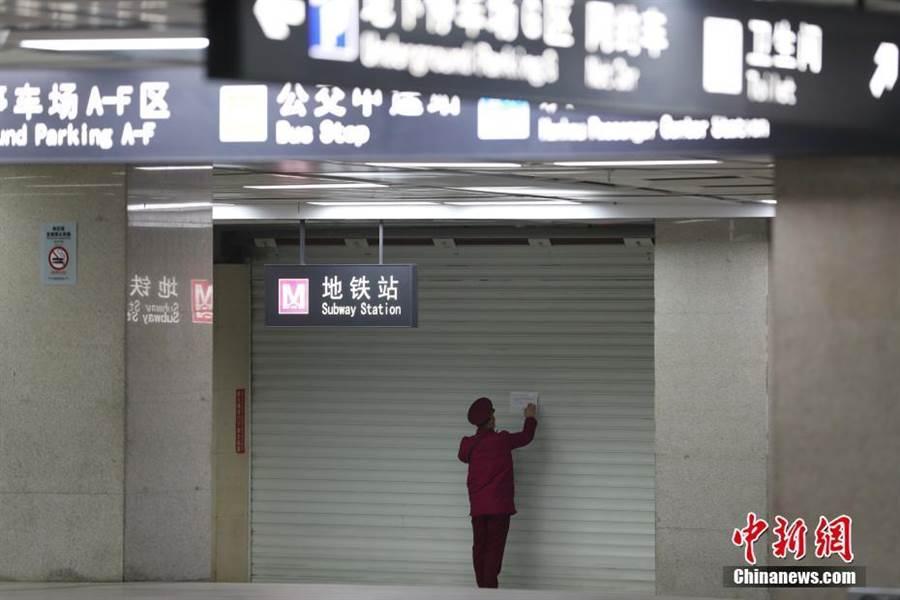 1月23日,武漢地鐵暫停運營,一名工作人員在拉下的門簾上粘貼公告。(圖/摘自中新網)