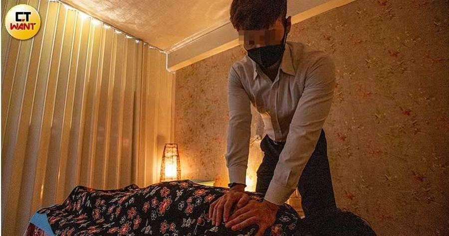 阿猛待女客躺到按摩床後,細心、用力地幫女客按摩。(圖/鄭清元攝)