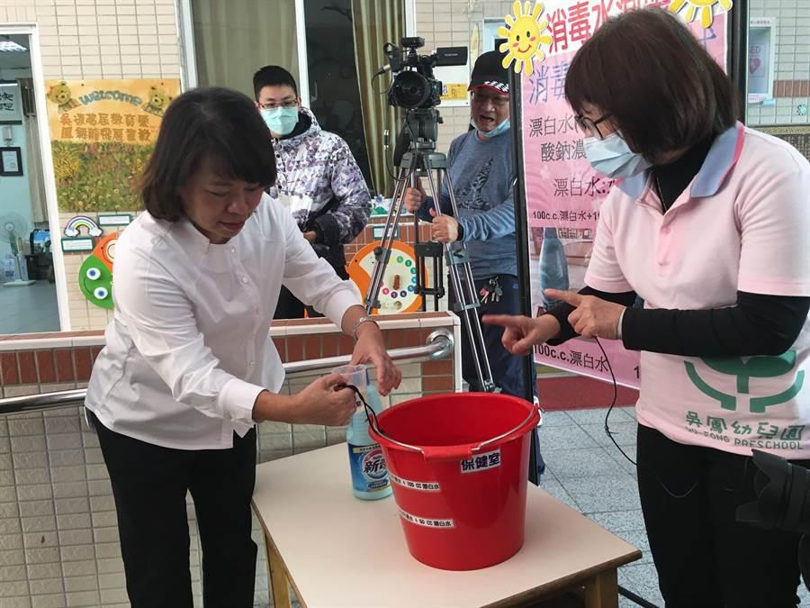 嘉義市長黃敏惠示範漂白水稀釋後再使用。(廖素慧攝)