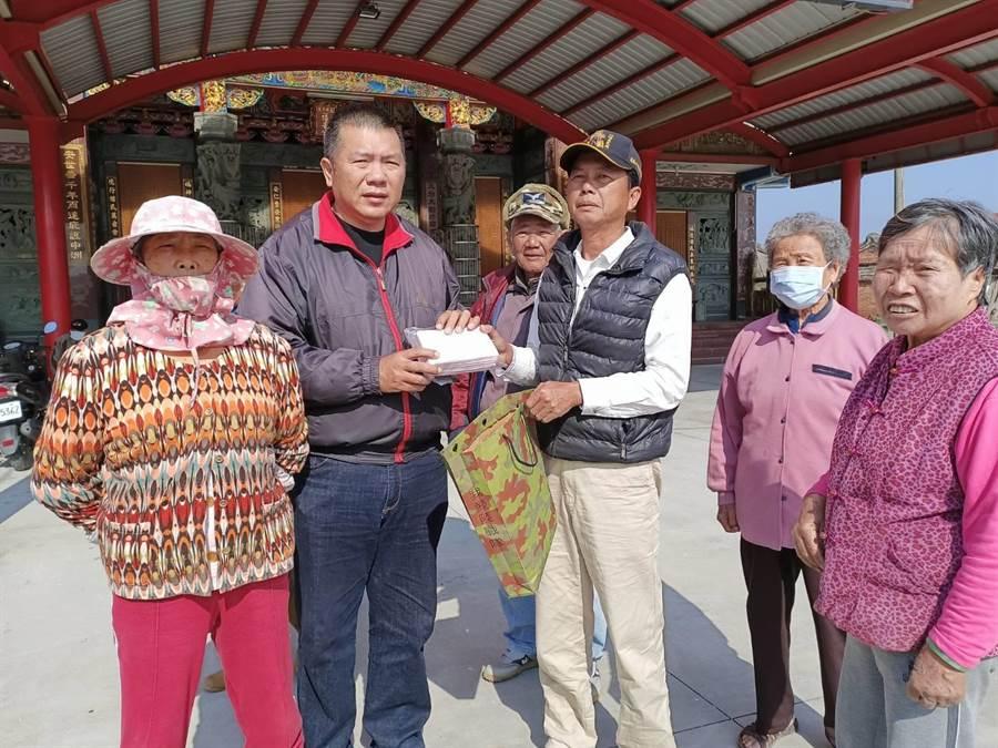 水上救難協會前理事長呂文正(左二)3日到東石鄉東崙村中洲社區免費發送200片口罩。(張毓翎攝)