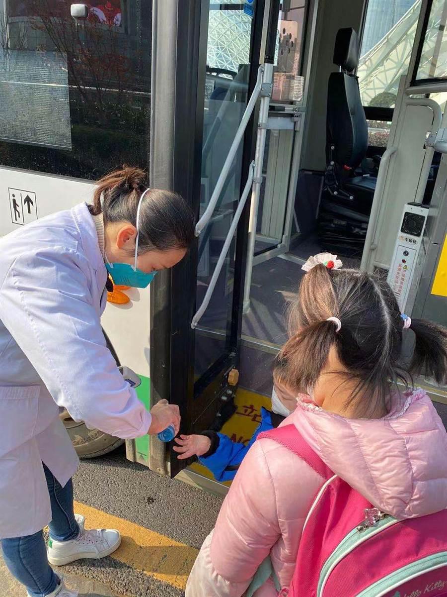 首批滯留武漢的200多名台人預計3日晚間搭機返台,一行人中午集結上車,準備前往機場。圖為2名首批返台的兒童在上車前消毒雙手。(台北家長會長協會提供)(中央社)