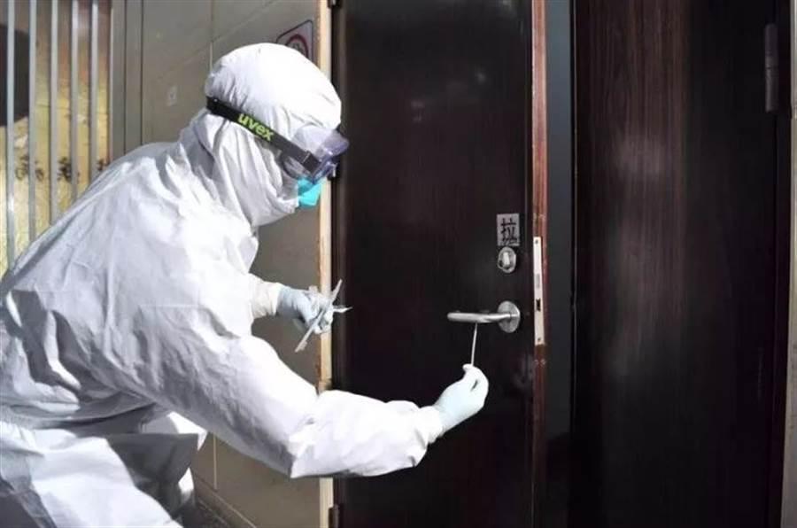 廣州疾控中心人員演示在門把上採集武漢肺炎的過程,這也是首次在人體外採集到新型冠狀病毒核酸。(圖/廣州日報)