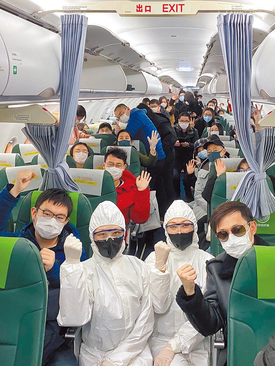 滯留武漢的台灣人終於可撤回台灣,海基會前董事長洪奇昌昨日指出,這成果得來不易。圖為2月1日淩晨,在從東京羽田機場飛往武漢天河機場的航班上,旅客與機組乘務人員合影留念。1月31日,大陸外交部會同有關部門和有關駐外使領館,緊急協調派出3架次包機,從泰國曼谷、馬來西亞沙巴州、日本東京等地分別接回滯留海外的湖北同胞共310人。    (新華社)
