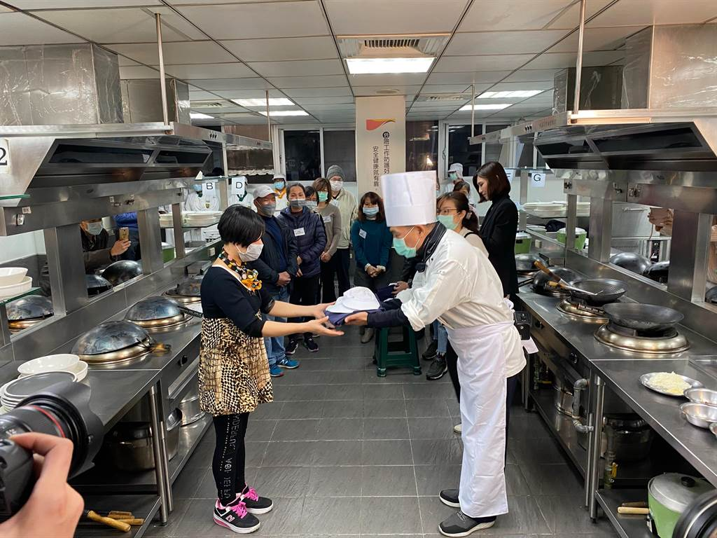 侯友宜逐一將廚師袍頒給新北市七所學校校廚。(戴上容攝)