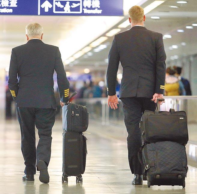 武漢肺炎擴散全球,不少國家喊卡中國航班。圖為2名航空機師5日結束飛行任務後,準備離開桃園機場。(范揚光攝)