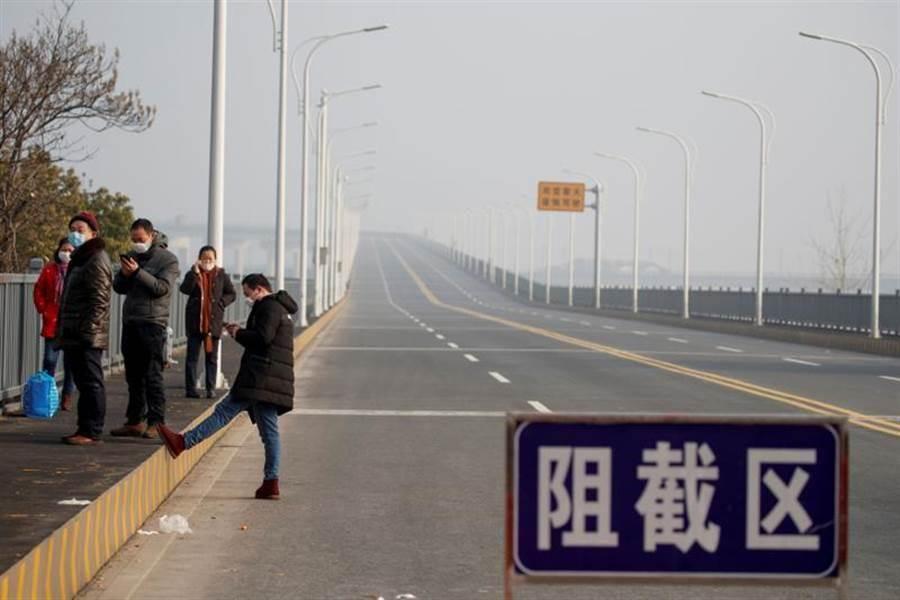 圖為民眾從湖北沿著橫越長江的九江長江大橋,走到江西省的檢查站。(圖/路透)
