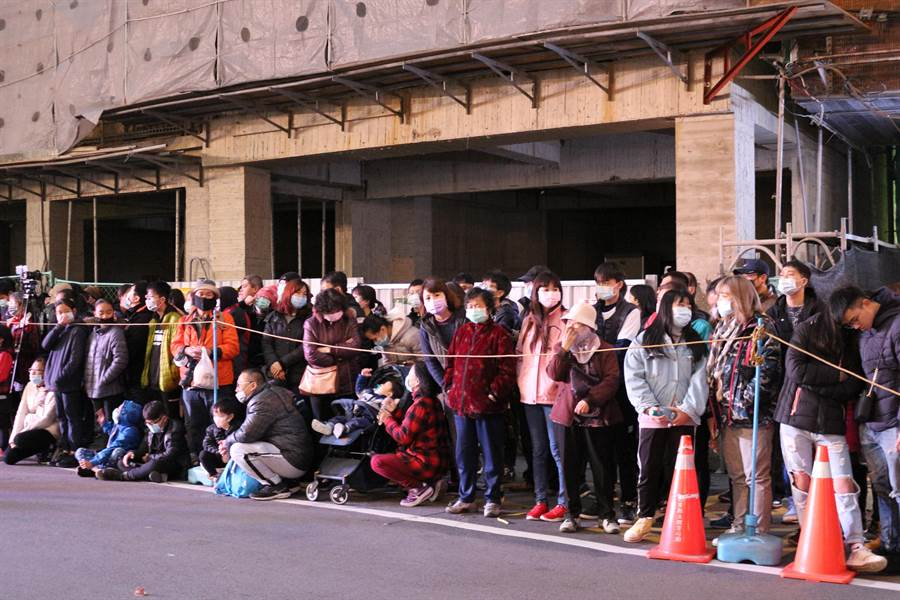 2020苗栗(火旁)龍「民俗踩街」活動7日晚間登場,民眾擠在路旁看踩街表演,不忘戴口罩防疫。(巫靜婷攝)