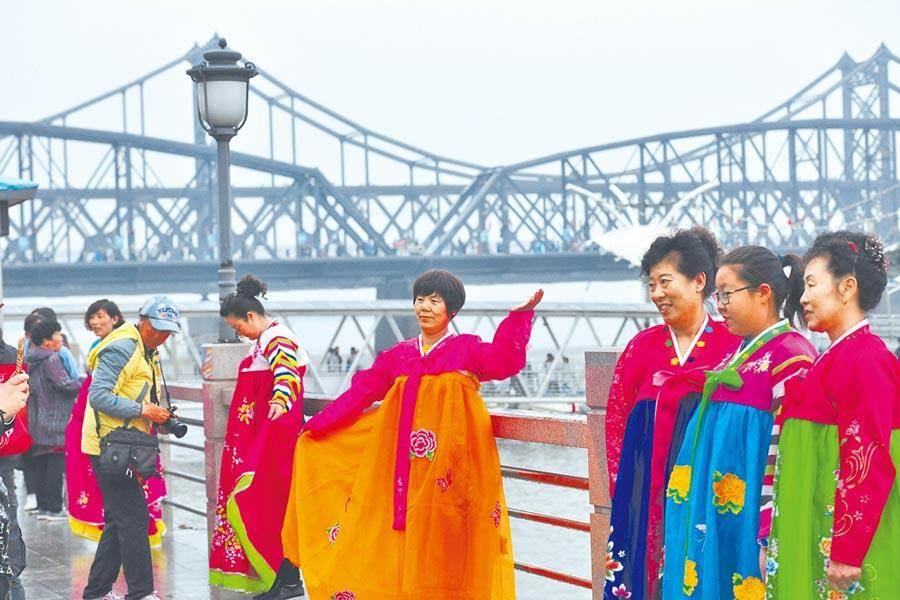北韓「鎖國」卻仍出現7例武漢肺炎確診病例。圖為遊客穿著朝鮮民族服裝拍照。(中新社)