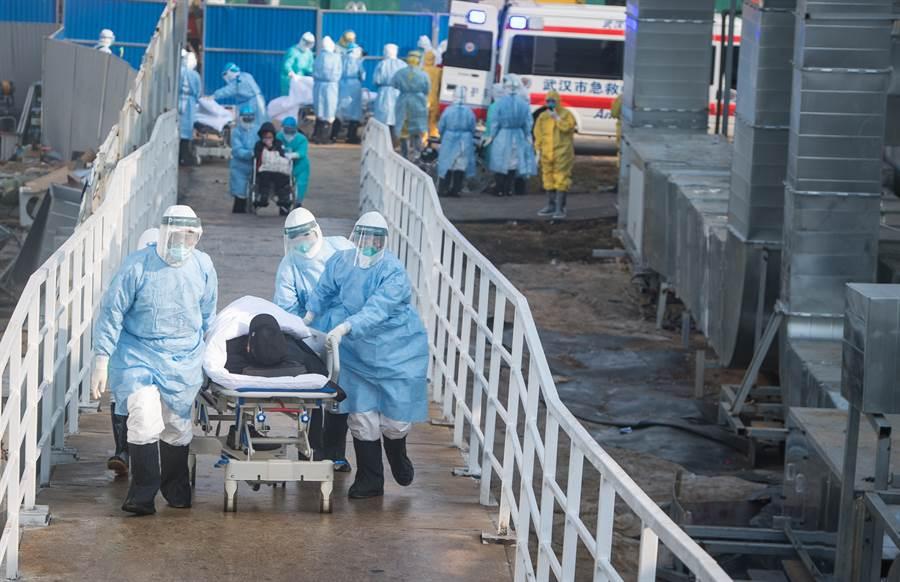 哈佛大學公衛專家丁亮警告,武漢肺炎疫情預測至少再持續一個月才達高原期。圖為陸醫護人員將患者轉運至武漢火神山醫院病房。 (新華社)