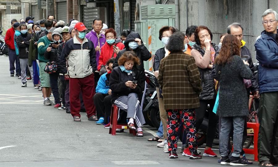 實名制購買口罩8日進入第3天,大批民眾在藥局外拉起長長的人龍排隊等候,當中以年長者居多。(姚志平攝)
