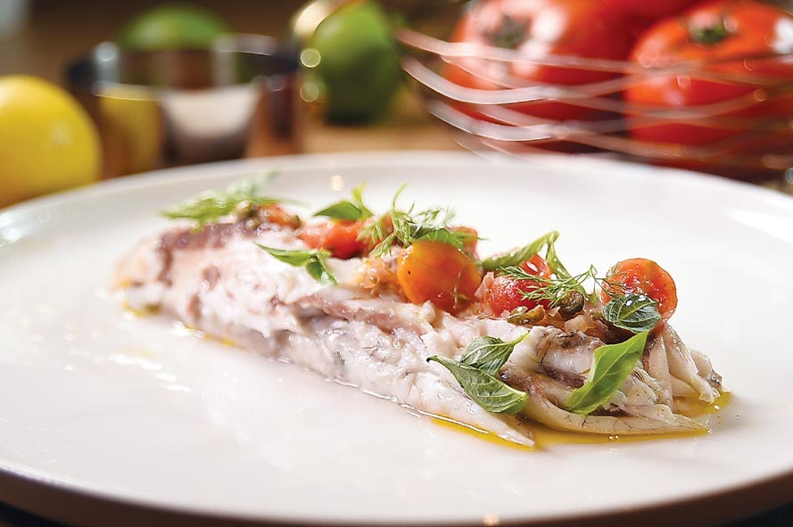 採桌邊服務、代客分切的〈鹽烤爐魚〉,會再搭配酸豆、去皮櫻桃番茄、並淋橄欖油後呈盤上桌。圖/姚舜