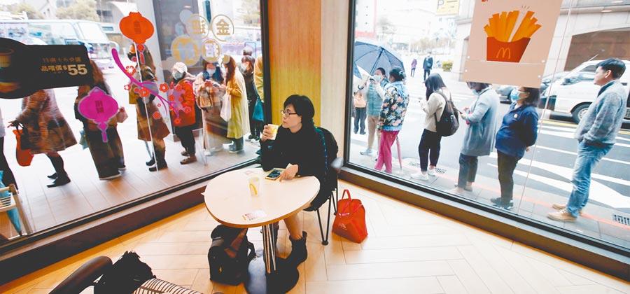 因應武漢肺炎疫情,各地健保藥局繼續第2天提供限量口罩供身分證號尾數奇數民眾購買,北市南京東路的一間藥局外下午開賣口罩前,就排滿長長人龍包圍了附近速食店的轉角。(鄭任南攝)