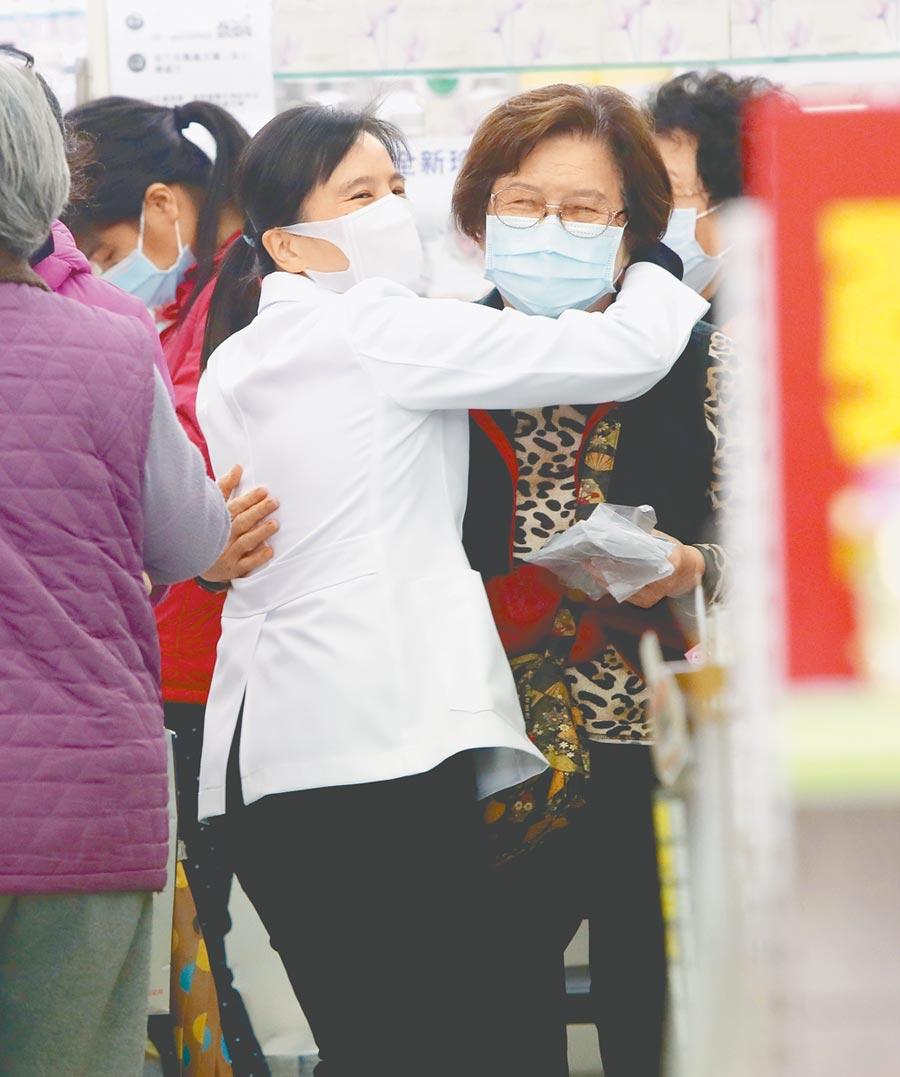 北市南京東路躍獅京東藥局的藥師鍾嘉芬(左),在開賣口罩前即忙東忙西幫排隊客人服務,一位排數小時的老顧客在開賣後迅速買到口罩,兩人高興得互相擁抱。(鄭任南攝)