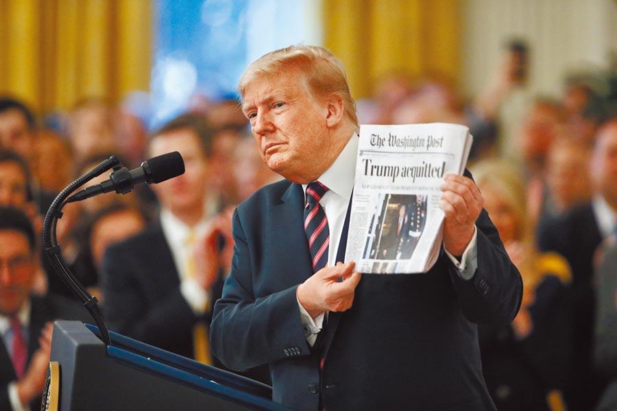 美國總統川普6日在白宮東廳手持當天的《華盛頓郵報》痛斥彈劾案可恥,該報頭版大字標題為「川普獲判無罪」。 (美聯社)