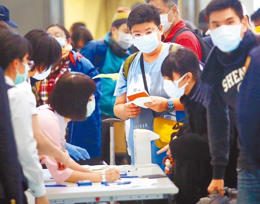 疾管署6日在臉書貼出機場防疫助理徵才廣告,吸引上千人踴躍報名,圖為護理人員(左)7日在桃園機場協助旅客填寫並回收入境健康聲明卡。(范揚光攝)