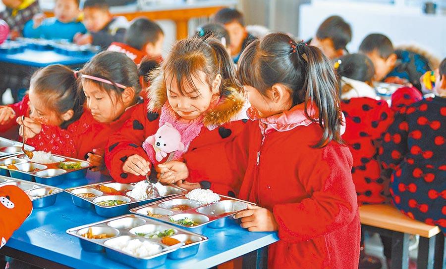 大陸目標2020年將「全面建成小康社會」。圖為安徽舒城縣曉天中心小學學生吃營養午餐。(新華社資料照片)