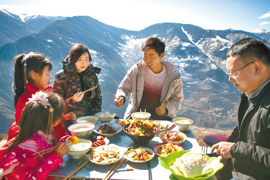 1月8日,張飛(右二)在四川美興鎮下馬廠村的農家餐廳與客人共進午餐。(新華社)