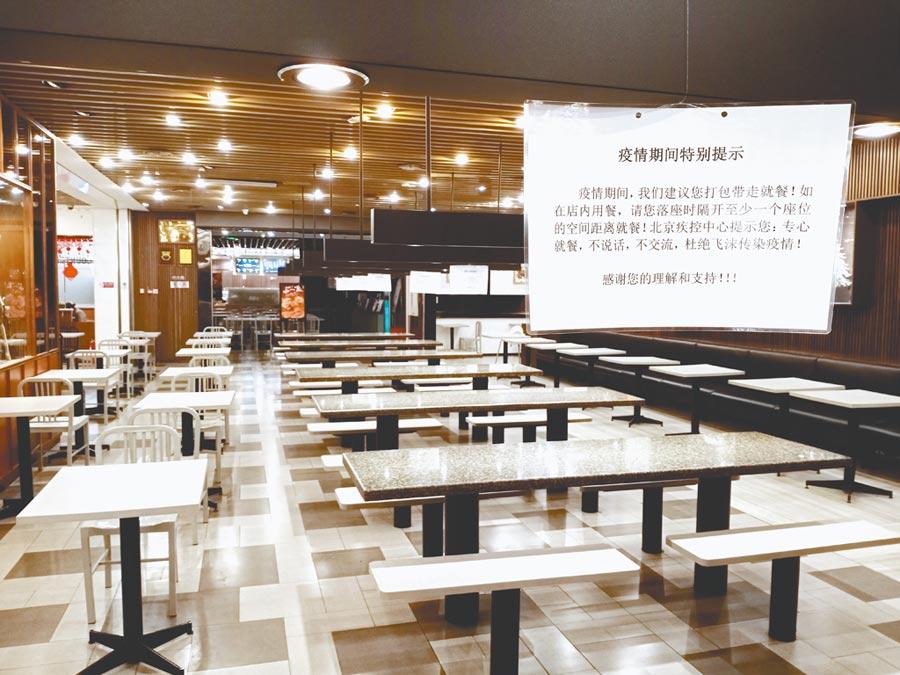 大陸為防控疫情,許多餐廳經營受衝擊。北京某商場美食街宣導間隔座位用餐或外帶,但用餐區空無一人。(記者陳君碩攝)