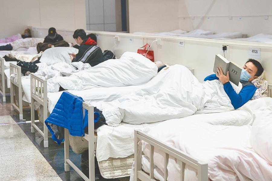 大陸新型肺炎確診者可補助6成醫藥費。圖為2月5日,武漢江漢方艙醫院的患者。(新華社)