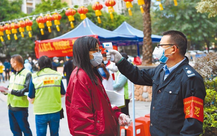 2月6日,廣州一社區的工作人員對進入社區的人進行體溫測量。(新華社)