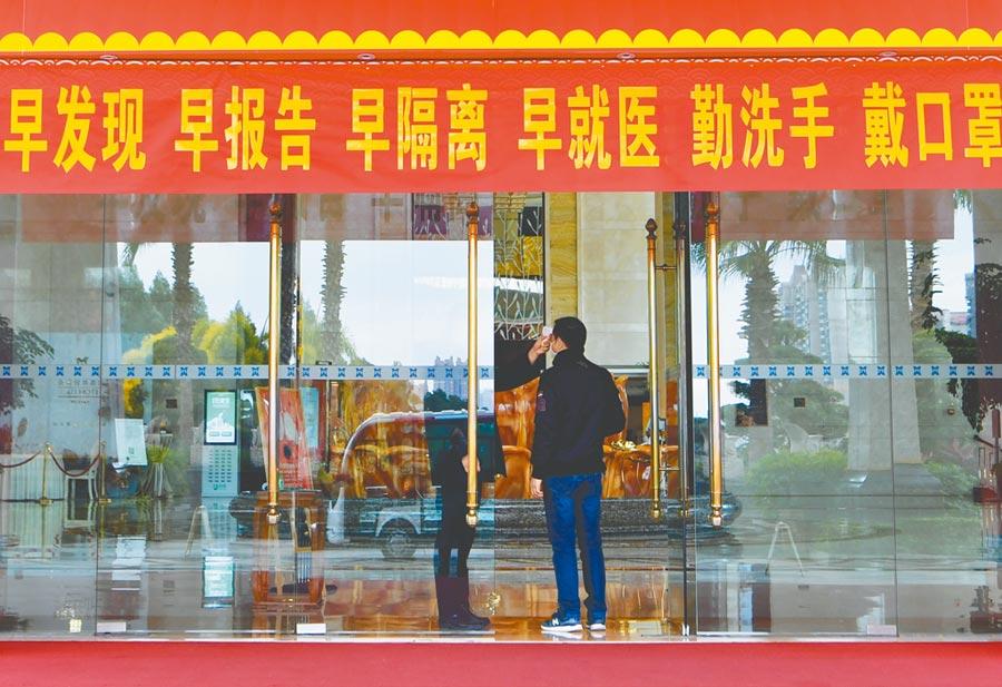2月6日,福建莆田一家酒店門口,工作人員對入住旅客進行體溫檢測。(新華社)