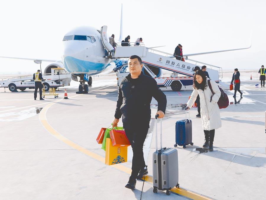新型肺炎疫情發燒,大陸機票退改總量達數百萬個,較平日成長近10倍。圖為1月17日,寧夏青年攜帶行李走出機場。(新華社)