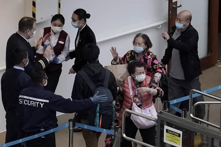 乘客9日在香港離開「世界夢」號遊輪。(美聯社)