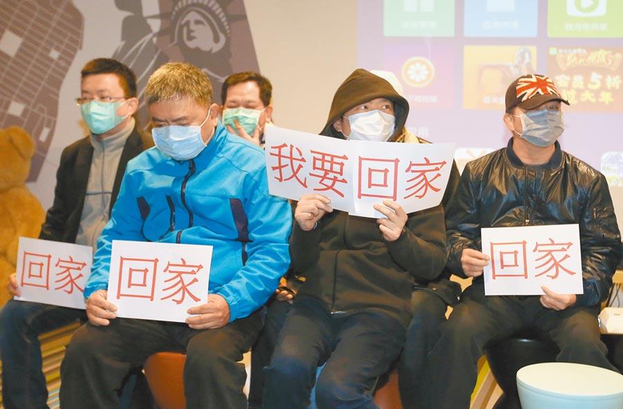 2月1日,滯留武漢民眾在台家屬手拿「回家」標語向外界求助。(本報系資料照片)