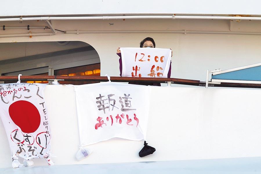 停泊在日本橫濱港隔離檢疫的「鑽石公主號」郵輪上,一名女子11日拿著一塊布上寫著該船離港時間。左邊布條上寫道「藥品缺乏」,右邊布條則寫「感謝報導」。(美聯社)
