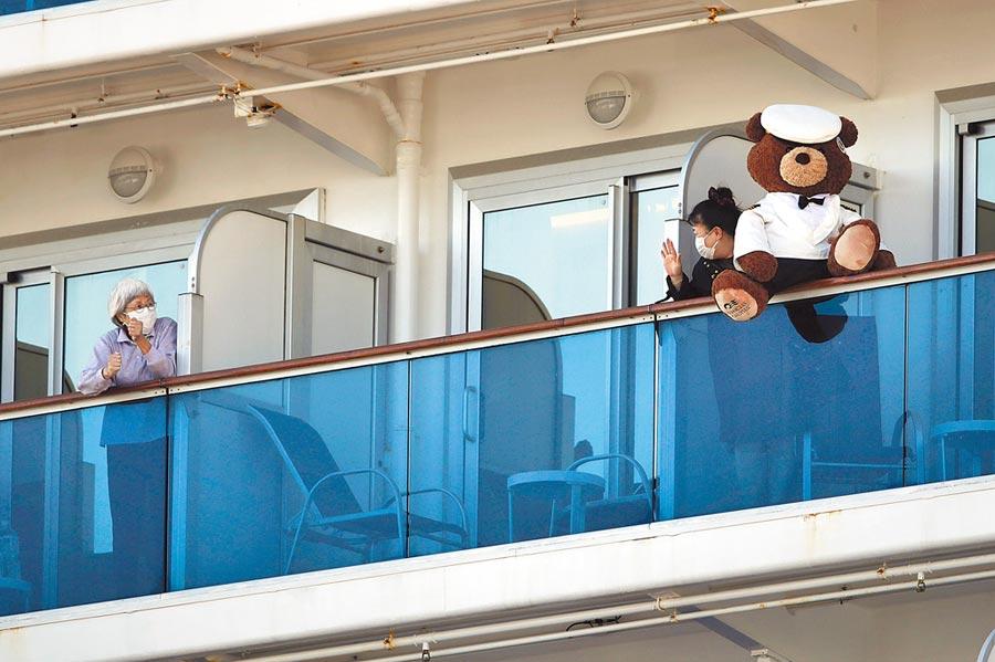 停泊在日本橫濱港隔離檢疫的「鑽石公主號」郵輪上,一名女子11日拿著一塊布上寫著該船離港時間。圖為一名女子拿著一只泰迪熊寶寶向另一名乘客揮舞。(美聯社)