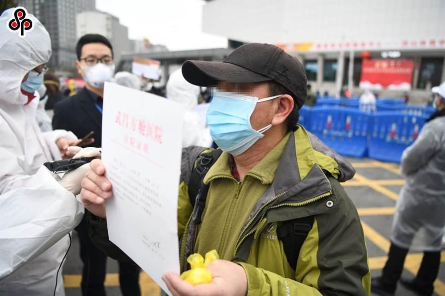 武昌方艙醫院首批新冠肺炎患者出院 2月11日,一名出院患者展示出院證明。(新華社)