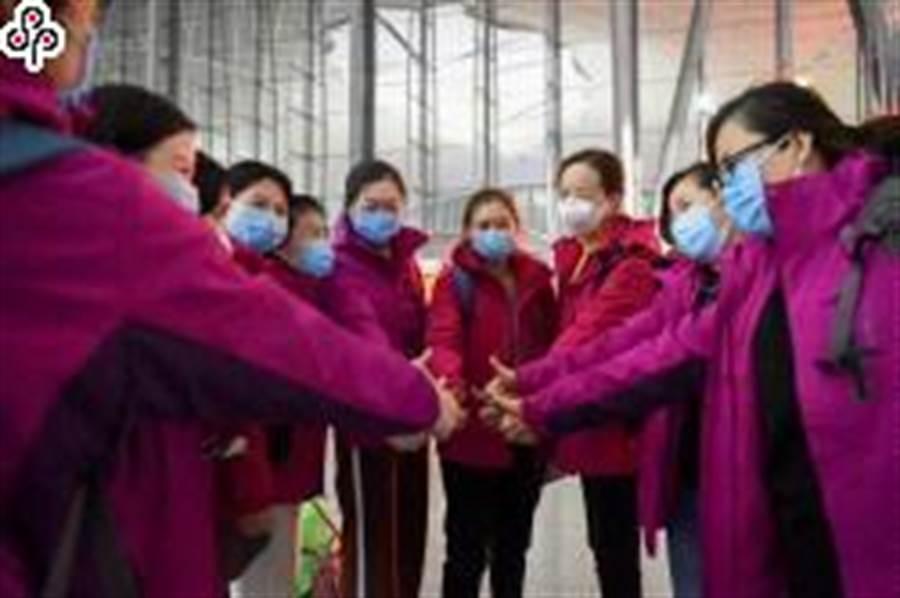 本月5日,新疆第二批援鄂醫療隊隊員在烏魯木齊地窩堡國際機場出發前相互加油。(照片取自新華社)