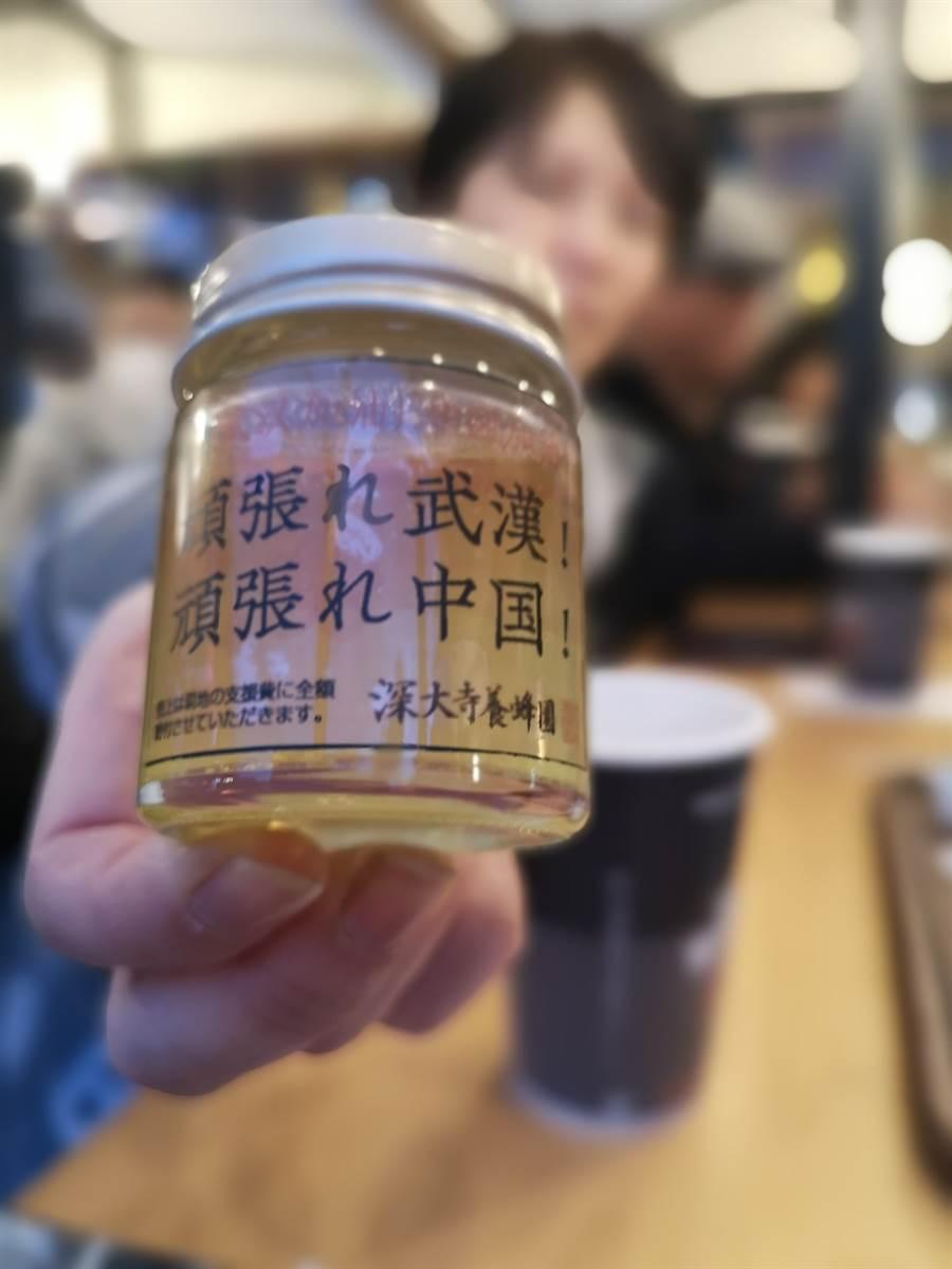 在日本東京池袋的元宵節慶祝活動現場,市民展示「為中國武漢加油攤位」上的蜂蜜。蜂蜜的包裝上寫著「武漢加油!中國加油!」。該攤位為中國抗擊新冠肺炎疫情向人們募捐,並將銷售蜂蜜所得全部捐出。(新華社)