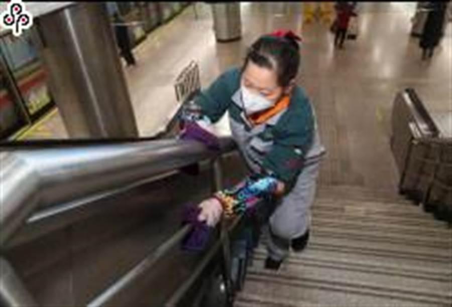 2月9日,在上海地鐵一號線徐家匯站,工作人員對樓梯扶手進行消毒。(照片取自新華社