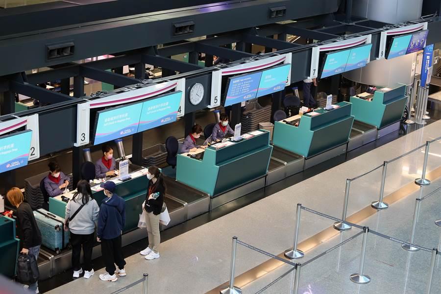 第二航廈華航旅客報到櫃台,原本應是旅客排隊等候報到的時段,目前只剩零星旅客。(陳麒全攝)